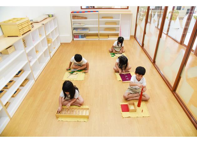 木製の玩具を使用したモンテッソーリモンテッソーリメソッドで学ぶ子供達
